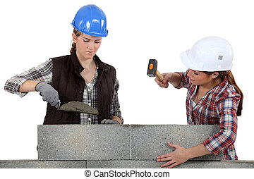 A team of tradeswomen laying cinder blocks