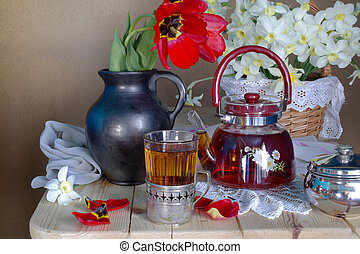 A teapot and a Cup of tea with a bouquet of spring flowers