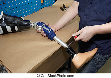 A technician adjusts a prosthetic foot. - Worker in...