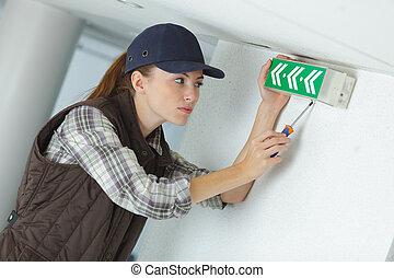 a technician installing emergency sign