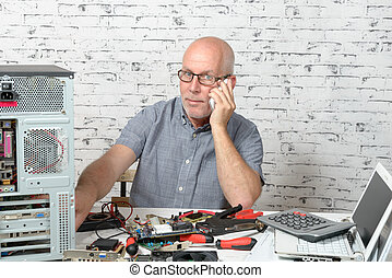 a technician repairing a computer and phone to the customer