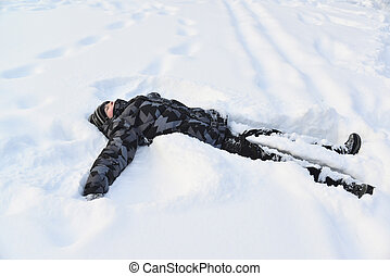 Teen boy lying in the snow