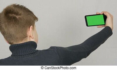 A teen boy stands with his back to the camera and is holding in hand a black smartphone with a green screen on white background. Teen Selfie