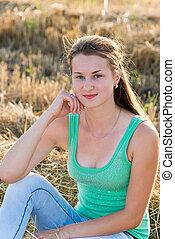 Teen girl resting in a field