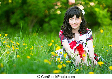 A teen girl sitting in the grass