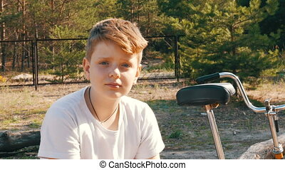 A teenage boy sits in forest summer park next to a bicycle...