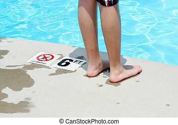 Teenage boy standing by a swimming pool