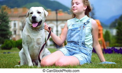 A teenage girl hugs her dog in the park. The dog licks and kisses the girl.. A teenage girl is playing with her favorite dog in the park. He is a devoted friend of man.
