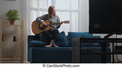 A teenage girl in a gray sweatshirt and black pants plays a calm melody on an acoustic guitar. Sits on the back of a blue sofa with bare feet. The sun is shining from the window behind.