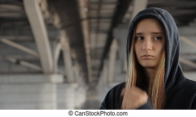 A teenage girl in a hoody with the hood on and loose...