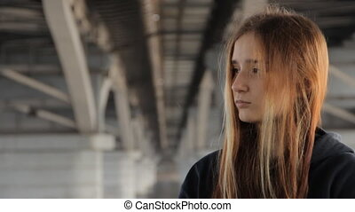 A teenage girl in a hoody with the loose multicolored hair...