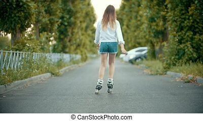 A teenage girl in rollerblades skating on the empty road....