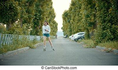 A teenage girl in rollerblades skating on the road - looking...