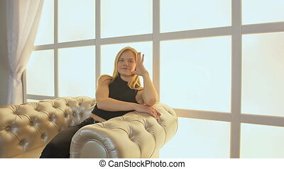 A teenage girl is posing in a soft chair of a photo studio.