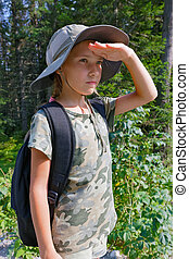 A teenage girl is traveling through the forest