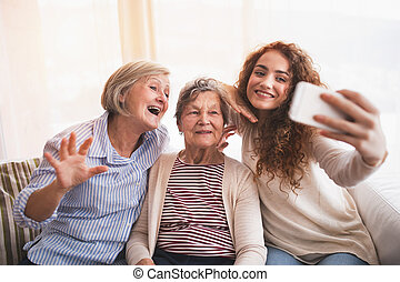 A teenage girl, mother and grandmother with smartphone at...