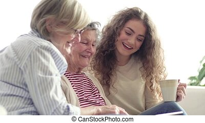 A teenage girl, mother and grandmother with tablet at home....