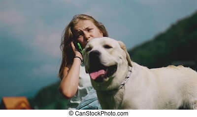 A teenage girl talks on the phone and plays with her favorite dog in the park. He is a devoted friend.