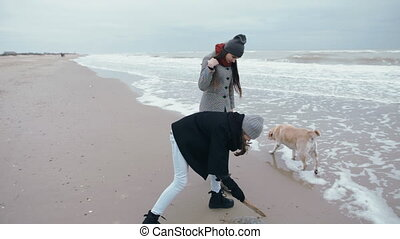 A teenage girl touches an dead jellyfish with a stick. Walking along the beach with mom and dog