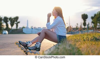 A teenage girl with a lollipop in roller-skates sitting on...