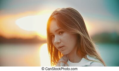 A teenage girl with light brown looking down - sunset. Close...