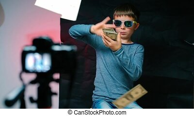 A teenager millionaire, video blogger makes a blog about making money. Holds a lot of US dollars in his hands and throws them.