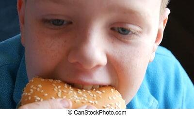 A teenager boy eats a hamburger in fast food restaurant,...