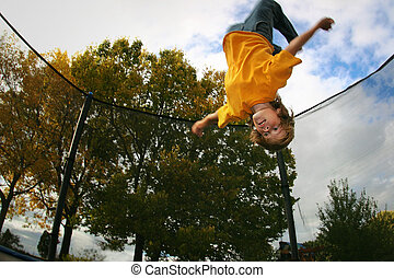 a teenager does a backflip on a trampoline