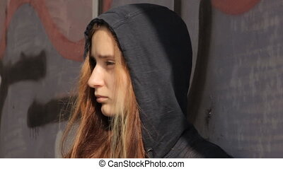 A teenager girl in a hoody with the hood on and multicolored hair against the graffiti