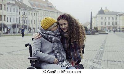 A teenager girl with disabled grandmother in wheelchair...