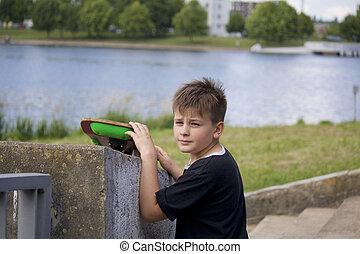 A teenager having fun with a skateboard on the asphalt.