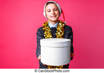 a teenager in a Christmas hat and tinsel on his neck, holding a Christmas gift close - up on a red background. the concept of Christmas to give gifts