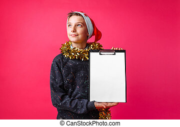 a teenager, in Santa's hat and with tinsel on his neck, holding a tablet with a clean sheet, makes plans for the New year on a red background