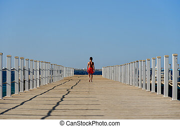 A teenager in shorts walks down the long pier to the sea