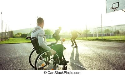A teenager in wheelchair looking at boys playing basketball...