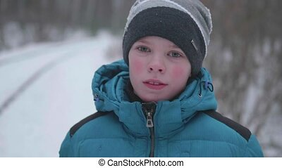 A teenager in winter Park, face closeup. Walking in the open air. A healthy lifestyle