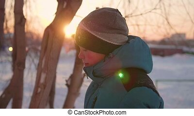 A teenager in winter Park talking and smiling . The time of sunset. Walks in the fresh air. Healthy lifestyle
