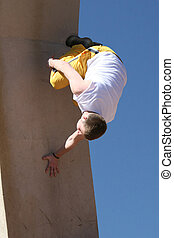A teenager performing a Parkour stunt. He is running up a wall and flipping in the air.