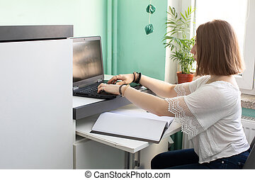 A teenager sits in front of a laptop with the intention of learning to live online.