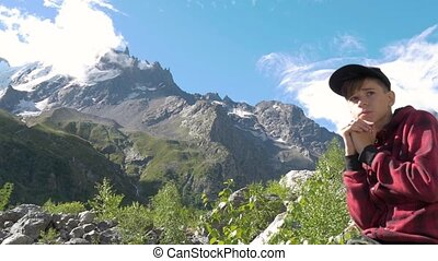 A teenager sits on the rocks and looks at the mountains.