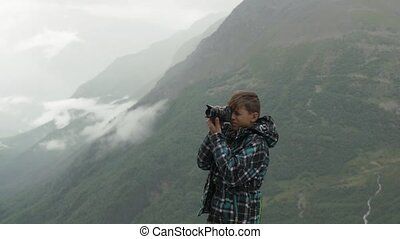 A teenager takes pictures of a mountain landscape.