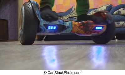 A teenager uses hoverboard in his home room. Spinning on a...