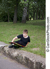 A teenager with a skateboard. Holds a skate in the hands.