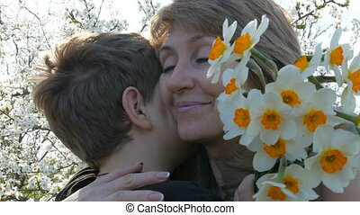 A teenager's son presents an adult middle-aged mom a bouquet...