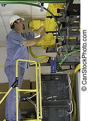 A telecommunication switch worker inspecting Fiberoptic...