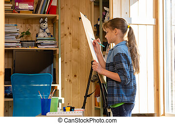 A ten-year-old girl draws on an easel at home