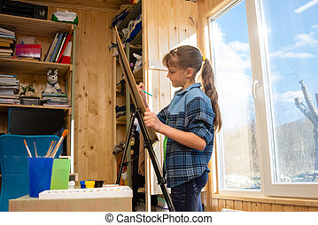 A ten-year-old girl draws on an easel by the wide window of the house