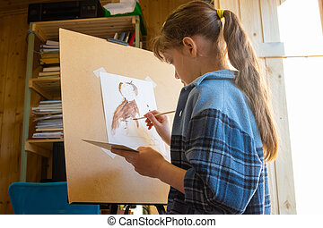 A ten-year-old girl draws with paints on an easel