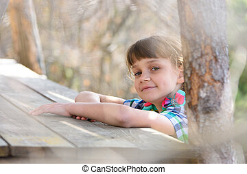 A ten-year-old girl sits at a wooden table in the forest and happily looked into the frame