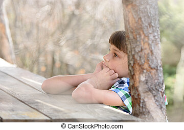 A ten-year-old girl sits at a wooden table in the forest and thinks